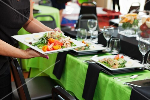 A waitress bringing Nicoise salad to a table