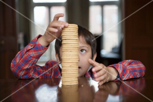 A boy stacking biscuits on a table