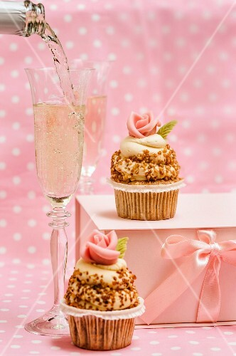 Cupcakes decorated with white chocolate topping and sugar roses being served with champagne