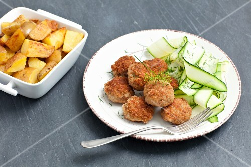 Meatballs served with a courgette salad and roast potatoes