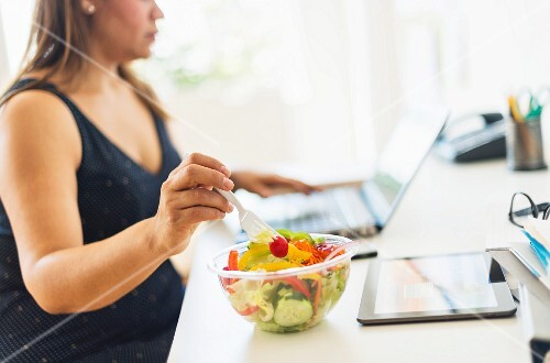 A woman working in a home office and eating salad