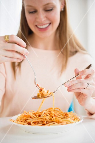 A young woman eating fettuccine with tomato sauce