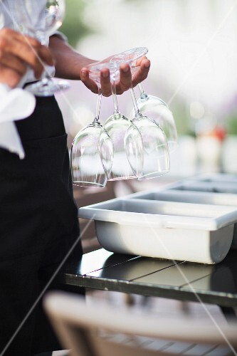 A waitress on the terrace of a restaurant holding wine glasses between her fingers