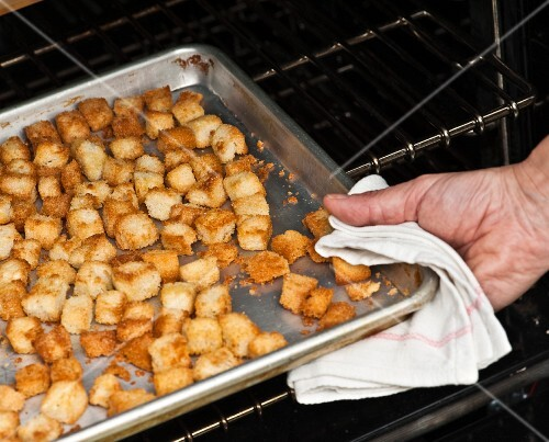 Croutons being removed from an oven