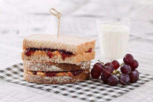 Peanut butter and jam sandwiches served with red grapes and a glass of milk (USA)
