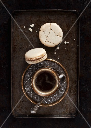 A cup of strong black coffee served with coffee macaroons