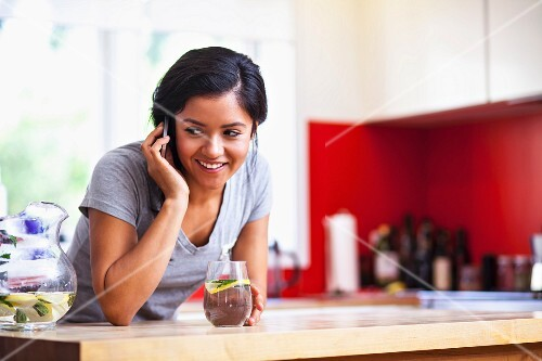 A young woman using a mobile phone in a kitchen