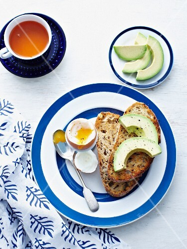A soft-boiled egg with toast and avocado
