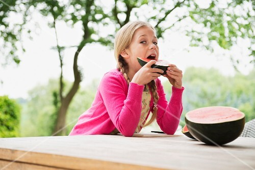 A girl outside eating a watermelon wedge
