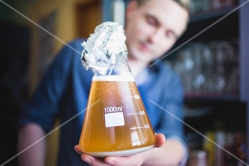 A man holding a bottle of yeast for making home-brewed beer