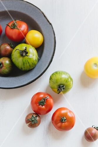 Various tomatoes on a plate and next to it