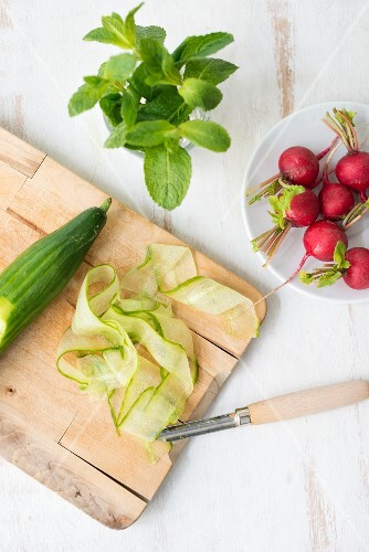Cucumber on a chopping board with radishes and mint