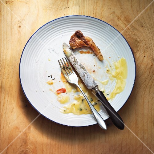 Remains of beef steak and Bearnaise sauce on a plate with cutlery