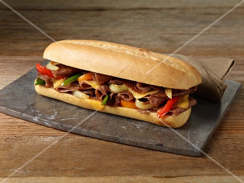A steak sandwich with red and yellow peppers
