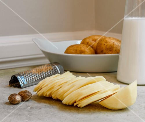 Ingredients for potato gratin: potato slices, nutmeg and milk