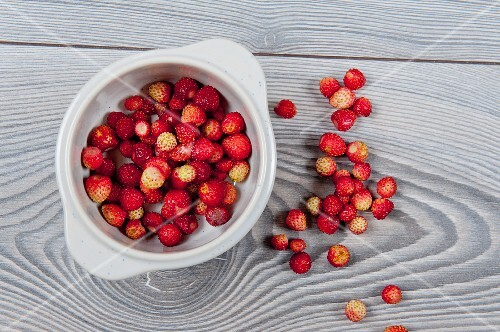 A bowl of fresh wild strawberries on a wooden surface