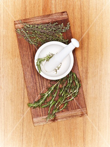 A mortar with fresh herbs on a wooden board (seen from above)
