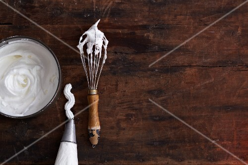 Beaten egg white in a bowl, a piping bag and on a whisk