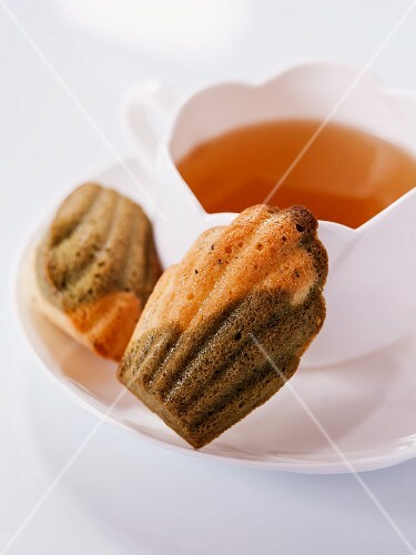 Bi-coloured tea madeleines on a saucer