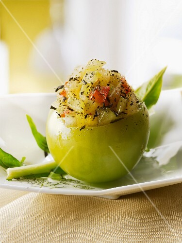 A green tomato filled with tomato tartar and green tea