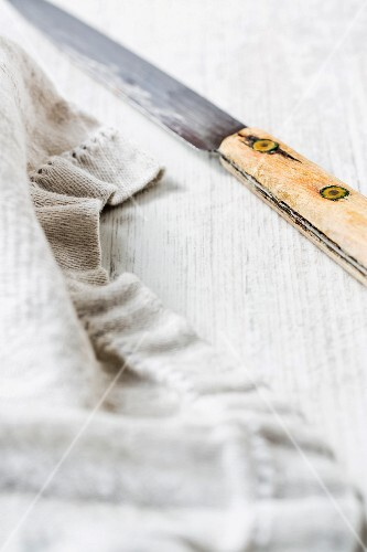 An old knife and a rustic tea towel on a wooden surface