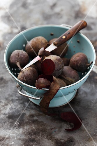 Cooked beetroots in a colander, one partially peeled