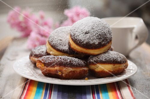 A plate of doughnuts dusted with icing sugar
