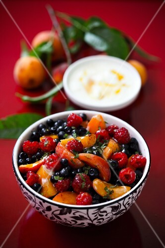 A summer fruit salad with peaches, raspberries and blueberries