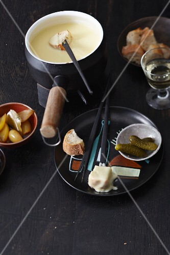 Classic cheese fondue with bread and mixed pickles