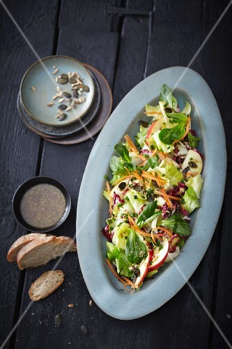 A winter mixed leaf salad with apples and seeds