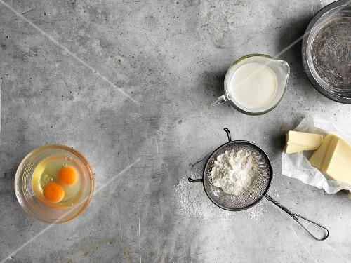 Various baking ingredients (egg, flour, cream, butter)