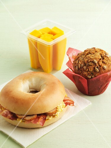 Bagel sandwich, muffin and fruit for breakfast