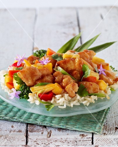 Sweet and sour chicken with peppers and baby corn on a bed of rice (Asia)