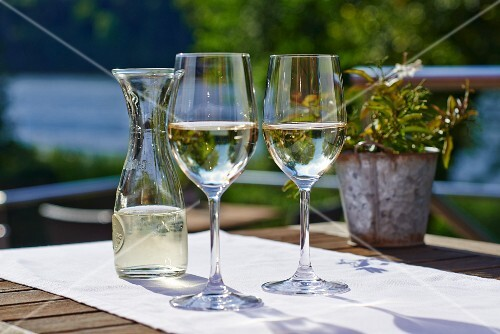 Two glasses of white wine and a carafe on a sunny terrace table
