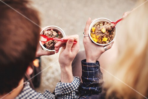 A couple eating frozen yoghurt, seen from above