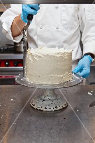Konditor bestreicht Torte mit Creme