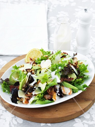 A mixed leaf salad with bacon, avocado and pine nuts