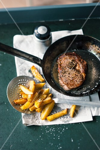 Steak in a pan with chips