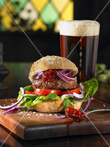 A burger with lettuce, tomatoes, red onions and chutney served with a pint of ale