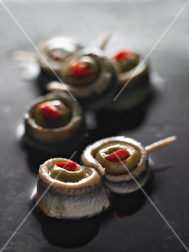 Anchovy rolls with olives on cocktail sticks