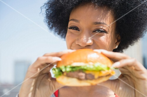 An African American woman eating a cheeseburger