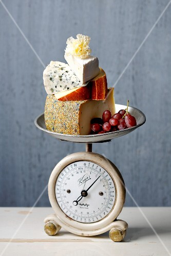 Various types of cheeses on a pair of old-fashioned kitchen scales