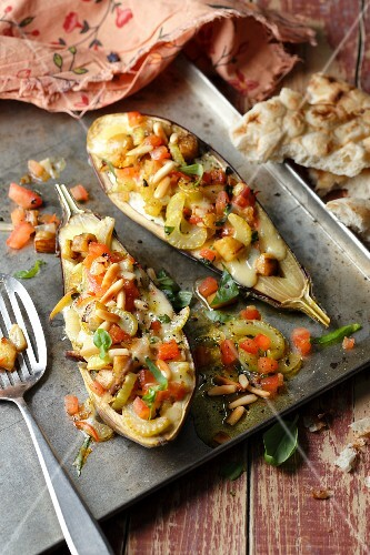 Aubergines filled with vegetables and pine nuts on a baking tray