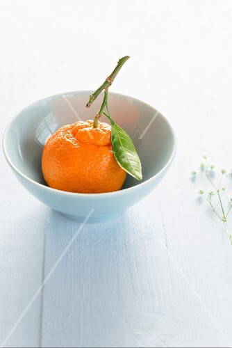 A tangerine in a bowl with a leaf