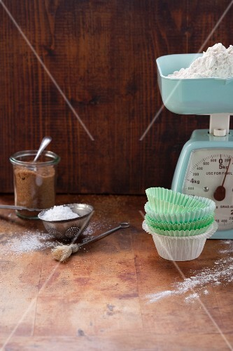 An arrangement of baking ingredients, a pair of scales and muffin cases