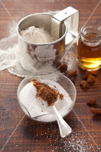 Baking ingredients: flour, sugar, cinnamon, honey and raisins