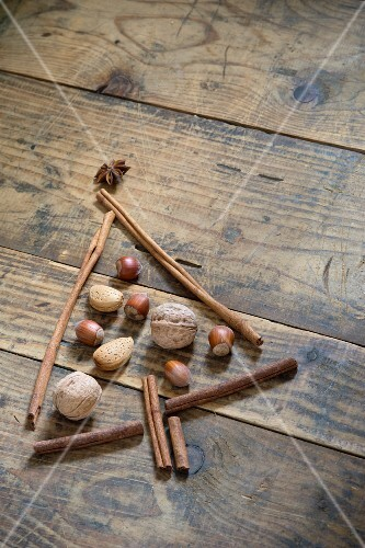 A Christmas tree made from nuts, anise stars and cinnamon sticks on a wooden table