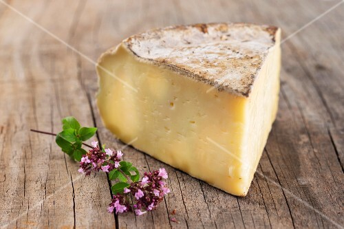 A slice of Tomme De Savoie cheese on wooden surface