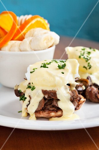 An English muffin topped with a poached egg, mushrooms and Hollandaise sauce served with oranges and bananas