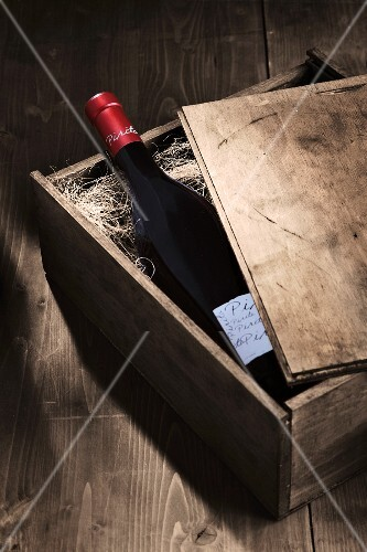 A bottle of red wine in an open wooden crate